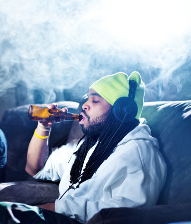 smoking marijuana and drinking beer amid clouds of smoke with copyspace photo