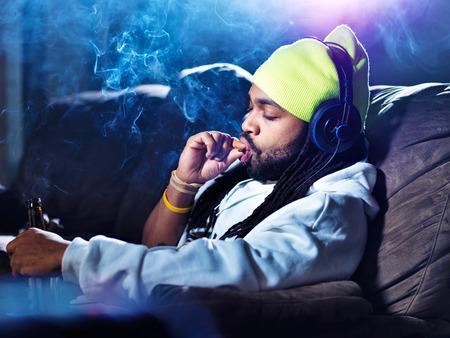 het roken van marihuana en bier drinken te midden van wolken van rook Stockfoto