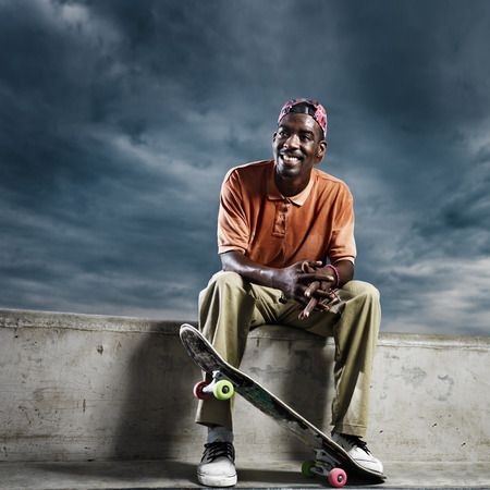 boarder: cool african skate boarder sitting down to rest