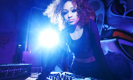 female club dj using turntable with headphones with lens flare photo