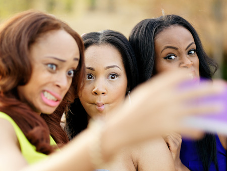young african girls making silly faces and taking pictures of themselves photo
