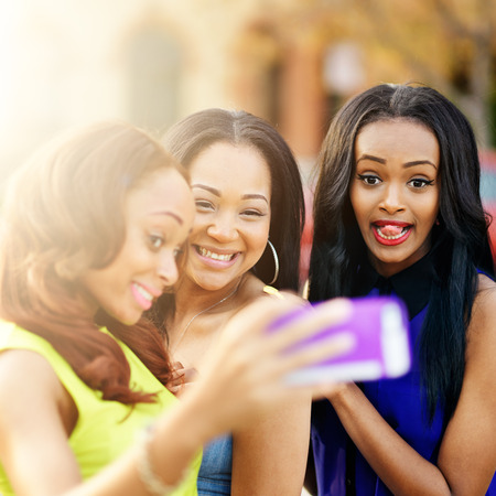 ebony: three african girls taking selfies with crazy faces Stock Photo