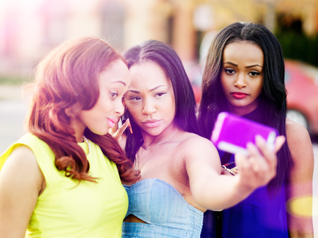 self communication: three african girls taking selfies with smart phone Stock Photo