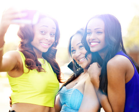 three african girls taking selfies with smart phone photo