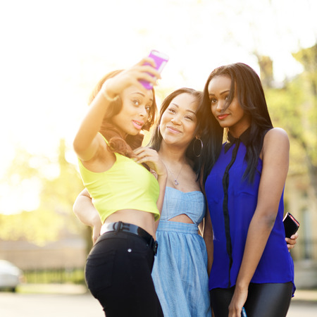 group picture: group of three girls wearing bright clothes taking selfies with smart phone Stock Photo