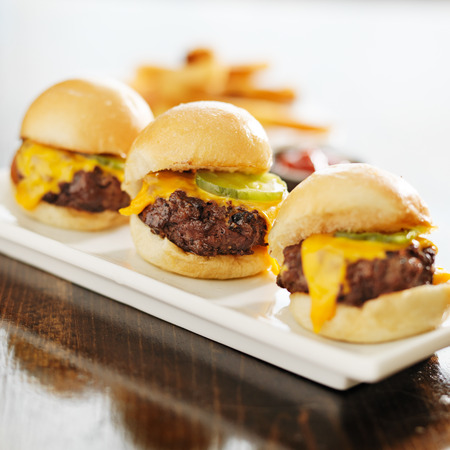 three burger sliders with cheese and pickle