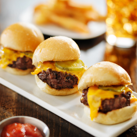 melted cheese: burger sliders with melted cheese and pickle Stock Photo