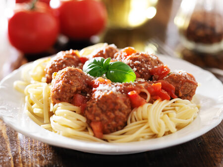spaghetti and meatballs with basil garnish photo