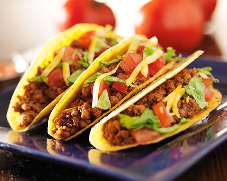 drie rundvlees tacos met kaas, sla en tomaten