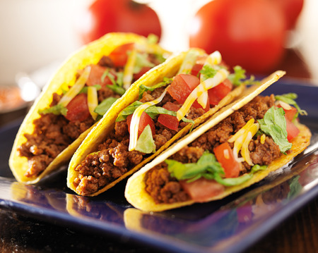 taco tortilla: three beef tacos with cheese, lettuce and tomatos Stock Photo