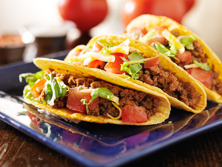 three beef tacos with cheese, lettuce and tomatos Imagens