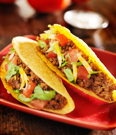 tacos: two beef tacos with cheese, lettuce and tomatos
