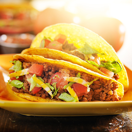 taco: two beef tacos with cheese, lettuce and tomatos