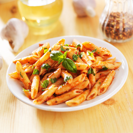 smothered: penne pasta smothered in tomato sauce Stock Photo