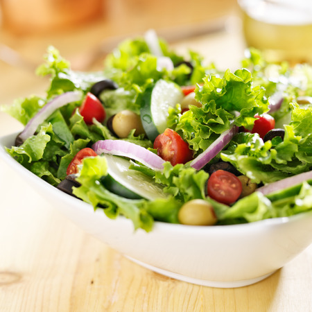 salad greens: bowl of leafy green salad with olives, tomatoes and cucumber.