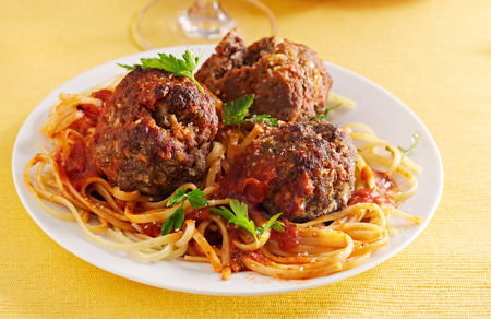 giant meatballs on spaghetti with parsley. photo