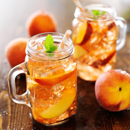 durazno: tarro de té de melocotón con rayas paja Foto de archivo