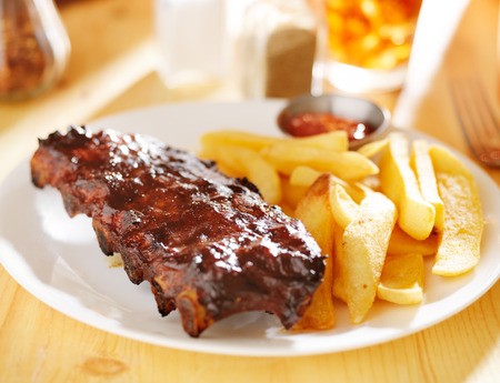plate with barbecue ribs and french fries photo