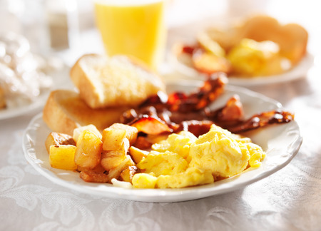 scrambled eggs: desayuno completo con huevos revueltos, patatas fritas y bacon,