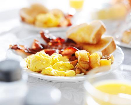 colazione: piatto di cibo per la colazione con pancetta, uova, pane tostato e patate fritte