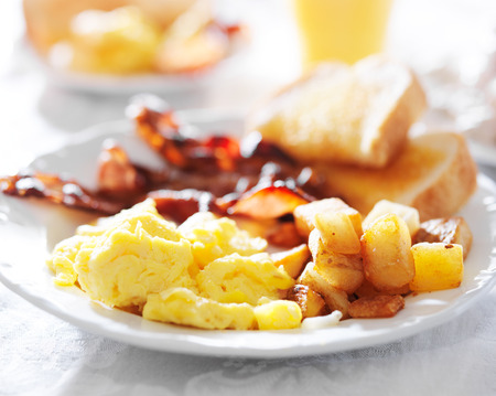 fried foods: breakfast with eggs, bacon, toast, and fried potatoes Stock Photo