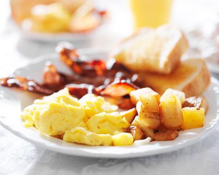 huevos fritos: desayuno con huevos, tocino, pan tostado y patatas fritas