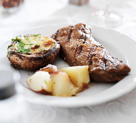 new york strip steak with potatoes and mushroom Фото со стока