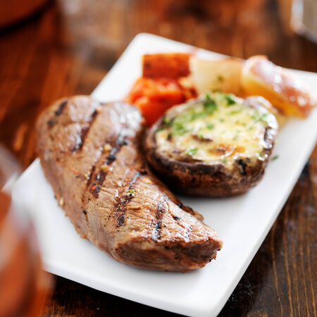 new york strip: grilled steak with potatoes and stuffed mushroom Stock Photo
