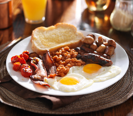 english breakfast with eggs, tomatoes, mushrooms, bacon, beans, and sausage