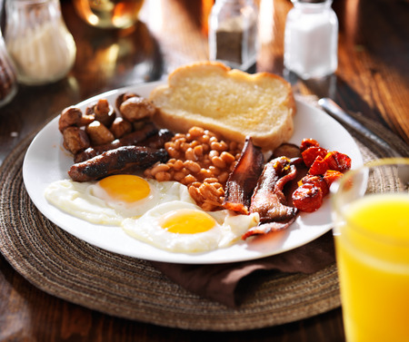 english food: english breakfast with eggs, tomatoes, mushrooms, bacon, beans, and sausage