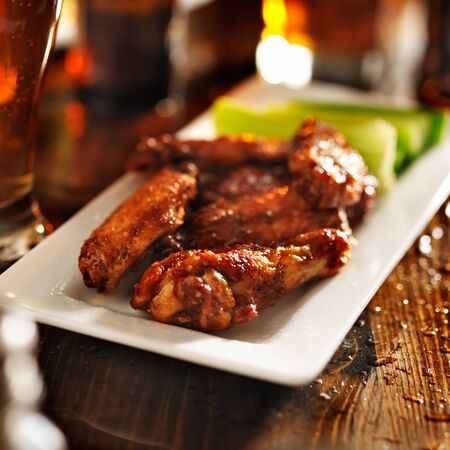 bbq chicken wings with celery on plate photo