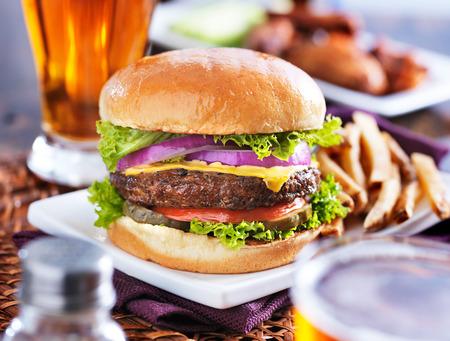 ハンバーガーとフライド ポテトとビールは背景の手羽先とパノラマ スタイルで撮影
