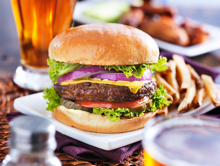 hamburger with fries and beer shot in panorama style with chicken wings in background Stock Photo