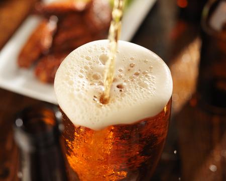 gieten bier in glas met bbq chicken wings op de achtergrond