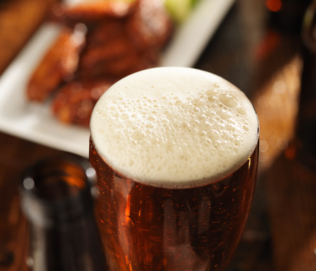 foamy: beer with foamy head and bbq chicken wings in background