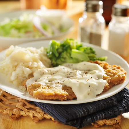 country fried steak with southern style peppered milk gravy Imagens