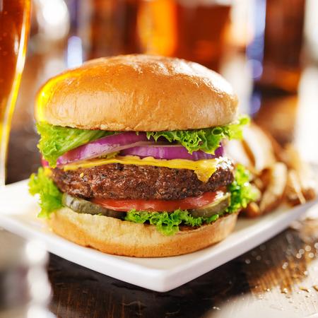 ビールとフライド ポテトとチーズバーガーをクローズ アップ