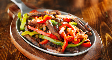 rustic food: mexican beef fajitas with bell peppers panoramic shot