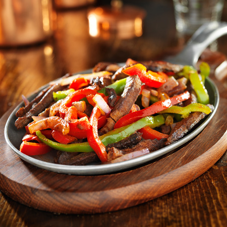 beef fajitas with green and red peppers in iron skillet