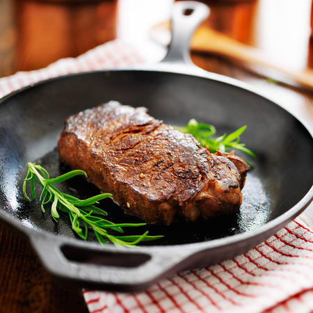 new york strip steak cooked in iron skillet 스톡 콘텐츠