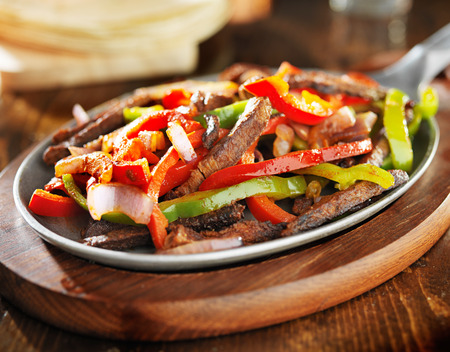 tortillas: mexican beef fajitas in iron skillet with tortillas in background