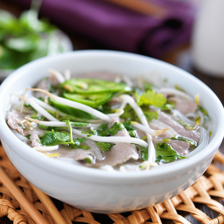 hot bowl of pho with beef and rice noodles photo