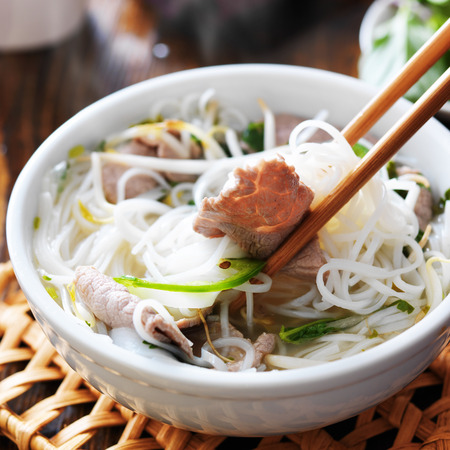 vermicelli: eating a bowl of pho with chopsticks Stock Photo