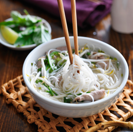 eating a bowl of pho with chopsticks photo