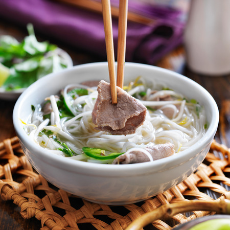 eating a bowl of pho with chopsticks and picking up beef Imagens