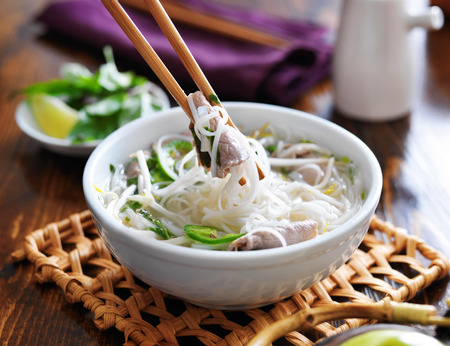 eating a bowl of pho with noodles and beef photo