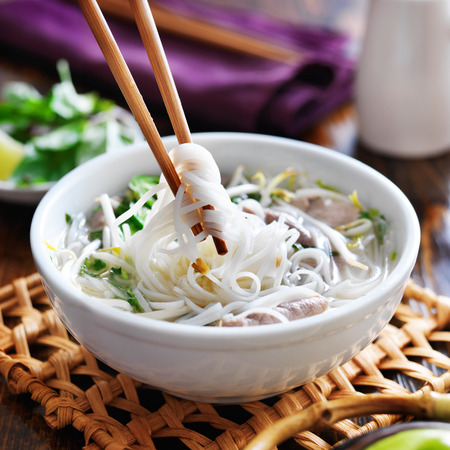 eating a bowl of pho with chopsticks Banque d'images