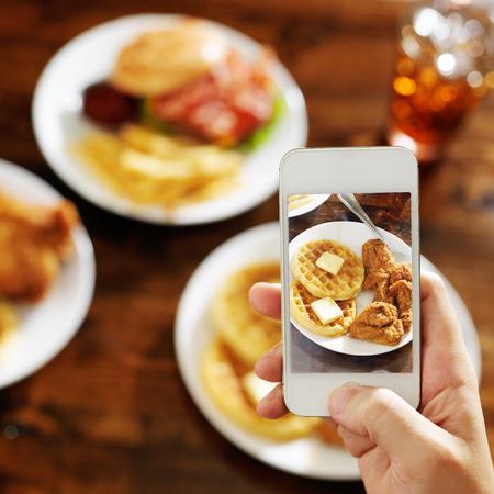 porno: prendendo foto di cibo con smartphone Archivio Fotografico