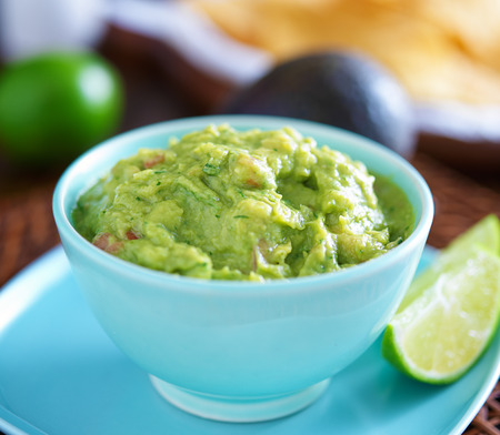 guacamole in colorful blue bowl with tortilla chips photo