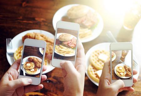 vrienden met smartphones om foto's van voedsel te nemen